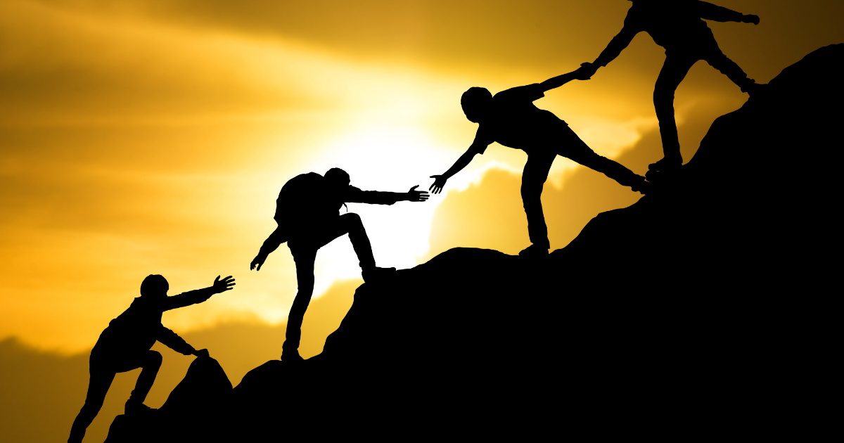 People helping each other climb mountain